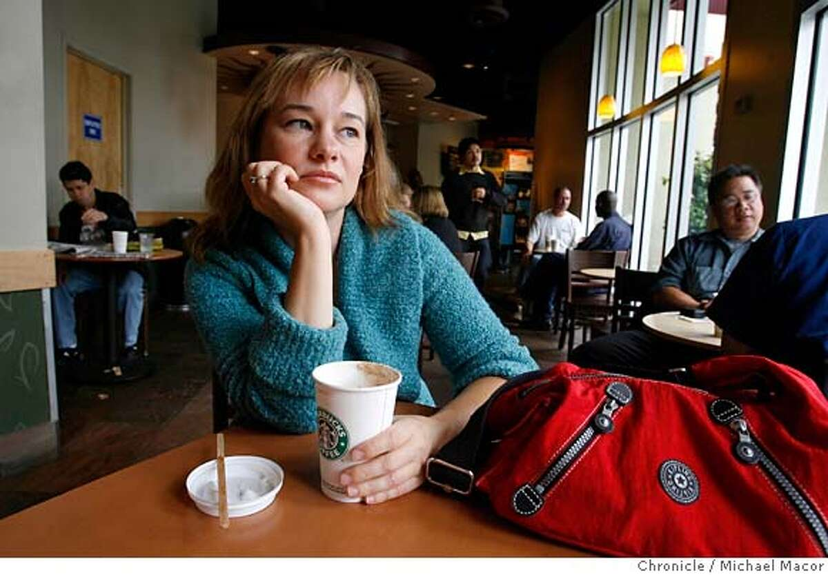 karen_030_mac.jpg Lodrick was at this Market St. Starbucks in the Castro, waiting for her coffee order when she noticed the alleged suspect, who was wearing the same faux fur coat in the bank photograph, standing right next to her. Karen Lodrick had her identity stolen. Her bank showed her a security camera photo of the women posing as Karen. She was wearing a distinctive coat. One day in a Starbucks Karen saw the woman in the coat and immediately called 911. When the women left Karen followed her, waiting for the cops. What ensued was a long chase through the city, onto and off buses and etc. Finally the cops showed up. Sure enough the woman had a wallet full of identification with her photo and Karen's name. (CQ) Karen Lodrick Photographed in, San Francisco, Ca, on 6/1/07. Photo by: Michael Macor/ The Chronicle Ran on: 06-15-2007 Above: Bank photo of person wearing a distinctive suede coat. Below: Karen Lodrick, latte in hand, sits in the Starbucks on Market Street where she spotted the suspect.