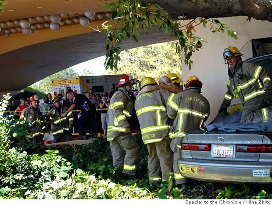 Bystanders at the Marin Civic Center watch as Novato resident Donald Hanahan, 88, is lifted from the wreckage of his Toyota by San Rafael rescue personnel Thursday afternoon, after the car he was driving crashed into the wall near the famed Center arches at the Marin County Courthouse. Photo by Nina Zhito/Special to the Chronicle  415 892 5443 Photo: Nina Zhito
