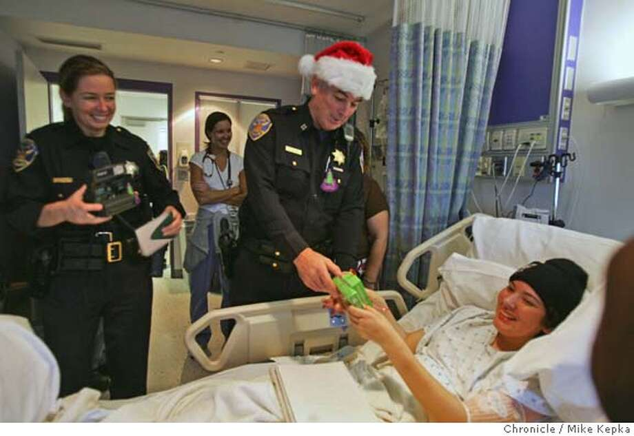SFPDtoys023seqn}_mk.JPG SFPD officers Laura Knight and Kevin Dillon deliver an iPod shuffle to UCSF children's hospital patient Salina Bajo, 16, who has been in and out of hospitals since July. Several officers from the Northern Station collected 100 toys for almost as many kids at UCSF Children's Hospital. Thursday they delivered the gifts to the hospital.  San Francisco on 12/22/05. Mike Kepka / The Chronicle MANDATORY CREDIT FOR PHOTOG AND SF CHRONICLE/ -MAGS OUT Photo: Mike Kepka