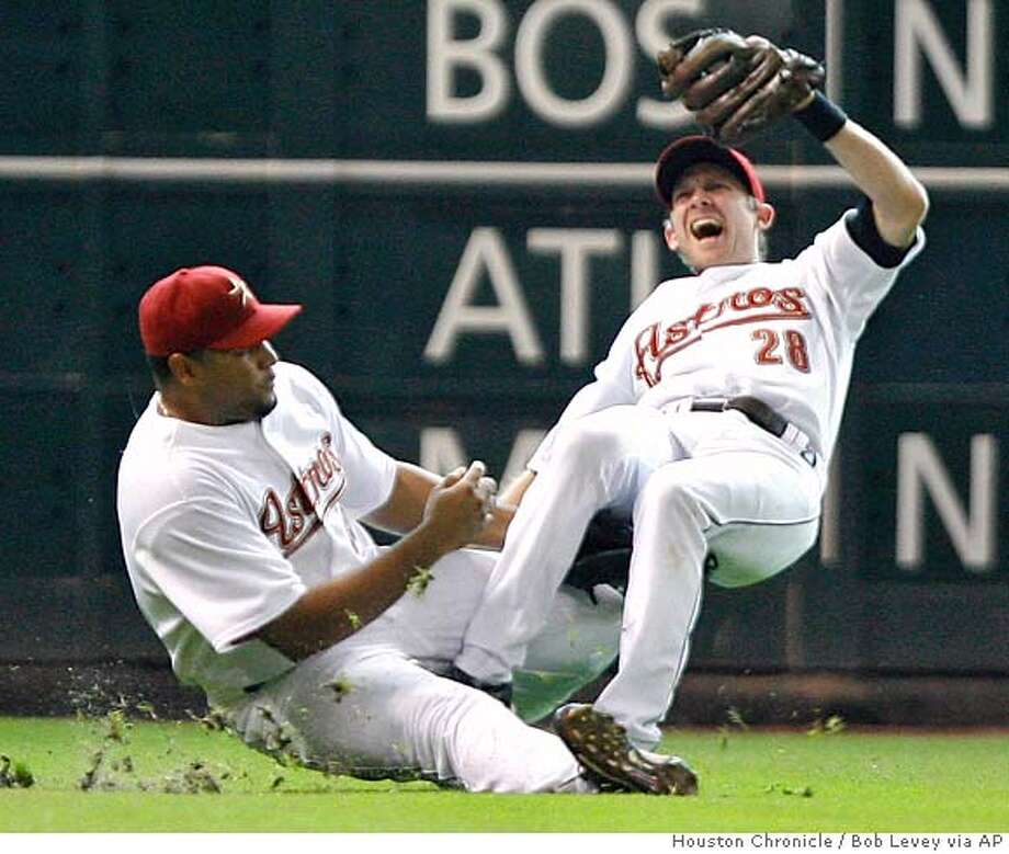 Houston Astros shortstop Adam Everett (28) and left fielder Carlos Lee (45) collide in the top of the fourth inning iof a baseball game against the Oakland Athletics Thursday, June 14, 2007, in Houston. Everett fractured his right leg and will be out four to eight weeks. (AP Photo/Houston Chronicle, Bob Levey) Photo: Bob Levey