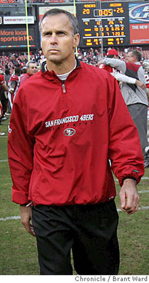 49ers204.JPG  49ers head coach Mike Nolan walks off the field, his team eliminated from the playoffs.  San Francisco 49er game action versus Arizona Cardinals Sunday December 24. The 49ers lost 26-20 eliminating them from the playoffs.  {Brant Ward/San Francisco Chronicle}12/24/06  Ran on: 06-15-2007  Mike Nolan has received the OK to wear a suit at home games and leave the team gear for the road. Photo: Brant Ward