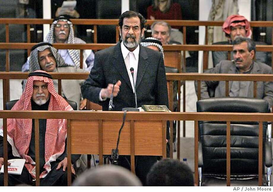 "Former Iraqi President Saddam Hussein, center, addresses the court during the resumption of his trial on Wednesday, Dec. 21, 2005 in Baghdad, Iraq. Saddam Hussein accused his American captors of torturing him, claiming at his trial Wednesday that he had been beaten ""everywhere on my body."" Saddam and seven co-defendants, background, are on trial in the deaths of more than 140 Shiites following a 1982 assassination attempt against him in the town of Dujail, north of Baghdad. (AP Photo/John Moore, Pool) Photo: JOHN MOORE"