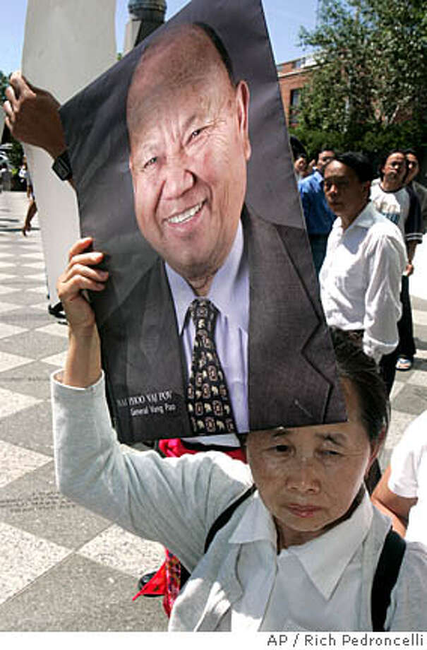 Ka Vang holds a photograph Gen. Vang Pao, who is being held on charges of trying to overthrow the government of Laos, as she joins others from Hmong community calling for his release during a demonstration outside the Robert T. Matsui Federal Courthouse in Sacramento, Calif., Monday, June 11, 2007. A magistrate judge ordered Vang Pao, 77, who led a Hmong fighting force that helped the CIA and American forces during the Vietnam War, detained until his trial. (AP Photo/Rich Pedroncelli) Photo: Rich Pedroncelli