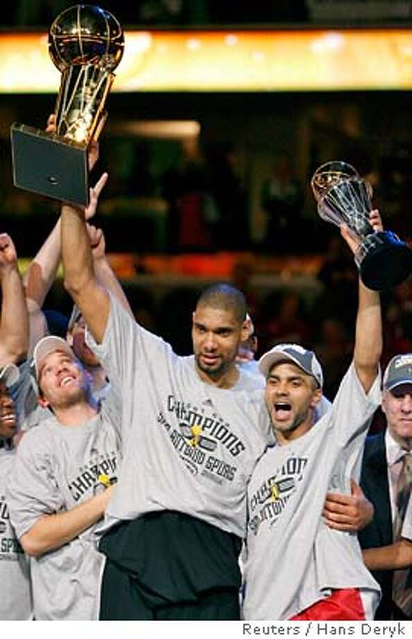 San Antonio Spurs' Tim Duncan (C) holds up the Larry O'Brien Trophy while teammate Tony Parker holds up his MVP trophy after defeating the Cleveland Cavaliers to win the NBA Finals basketball series in Cleveland, Ohio, June 14, 2007. REUTERS/Hans Deryk (UNITED STATES) Photo: HANS DERYK