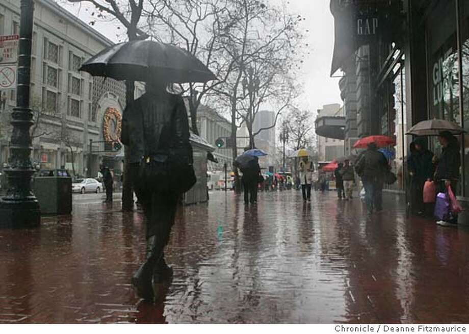 The heavy rains did not stop people around Powell Street from finishing their holiday shopping.  Event in San Francisco on 12/22/05.  Deanne Fitzmaurice / The Chronicle Photo: Deanne Fitzmaurice
