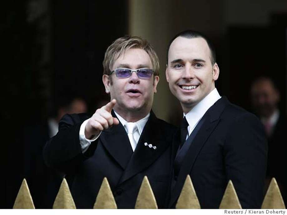 British pop star Elton John and his partner David Furnish leave the Guildhall in Windsor, southern England, after their civil ceremony December 21, 2005. John tied the knot with long-term partner Furnish on Wednesday, joining hundreds of gay couples in England taking advantage of a new law to formalise their relationships. REUTERS/Kieran Doherty 0 Photo: KIERAN DOHERTY