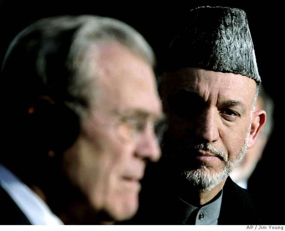 """U.S. Secretary of Defense Donald H. Rumsfeld holds a joint news conference with Afghan President Hamid Karzai in Kabul, Afghanistan, Wednesday Dec. 21, 2005. Rumsfeld, who flew to Afghanistan from Pakistan told reporters the United States is not going to abandon Afghanistan. Rumsfeld said that commitment includes helping run down the remaining Taliban and al-Qaida fighters that are still """"causing difficulties"""" for Afghanistan. (AP Photo/Jim Young, Pool) POOL Photo: JIM YOUNG"""