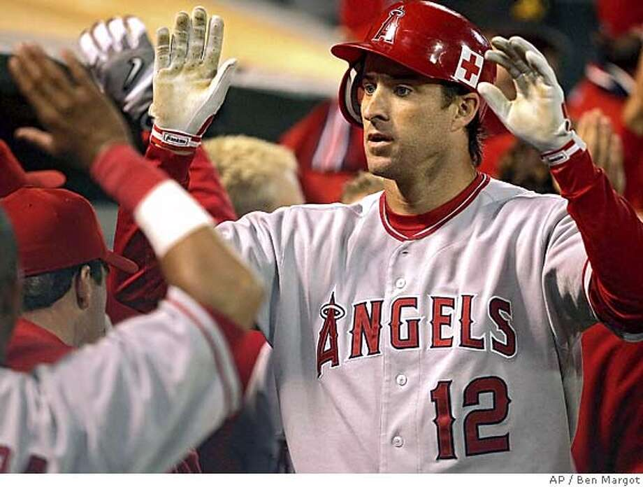 ** FILE ** Los Angeles Angels' Steve Finley (12) is congratulated by teammates as he returns to the dugout after his two-run homer against the Oakland Athletics in this Sept. 26, 2005, file photo in Oakland, Calif. The San Francisco Giants acquired Finley from the Angels on Wednesday, Dec. 21, 2005, for third baseman Edgardo Alfonzo in a swap of former All-Stars who dropped off dramatically last season. (AP Photo/Ben Margot) Photo: BEN MARGOT