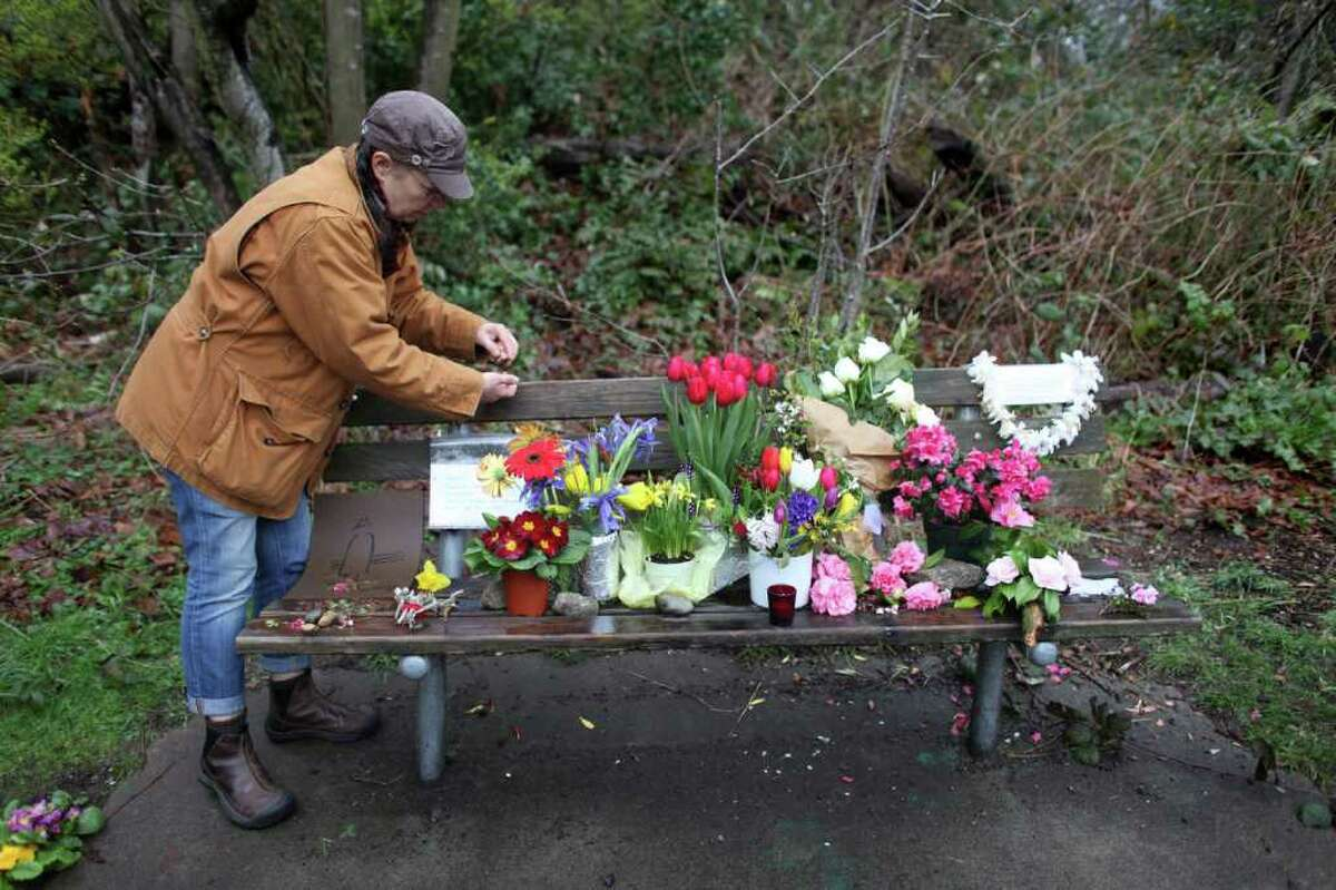 Jodi Waltier adds to a growing memorial for Alpha Lake Rajai, 59, a homeless man known by many for regularly sitting on the bench in Ravenna Park. On March 8th he was shot and killed. Dozens of neighbors and friends came out to honor Rajai on Sunday, March 18, 2012 during the memorial, some saying he was a warrior that guarded their park.