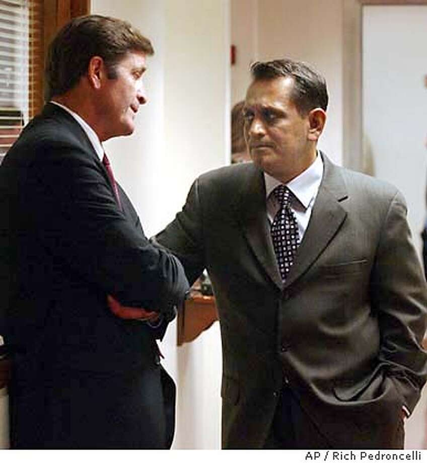 Insurance Commissioner John Garamendi, left, talks with state Sen. Gil Cedillo, D-Los Angeles, in a hallway outside the state Senate chambers at the Capitol in Sacramento, Calif., Friday, Sept. 12, 2003. On the last day of this years legislative session, the lawmakers approved the package of bills that Democrats say would cut the cost of treating job-releated inuries by at least 20 percent. (AP Photo/Rich Pedroncelli) Photo: RICH PEDRONCELLI