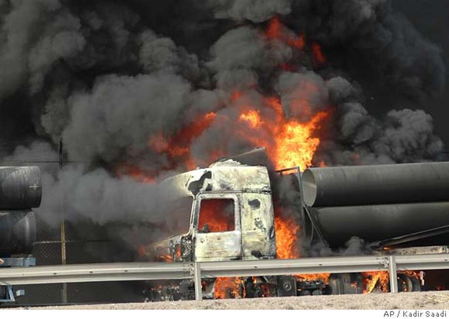 A Truck burns after the convoy carrying U.S. army supplies in Baghdad, Iraq, Tuesday, Dec. 20, 2005, was attacked. Assailants in Baghdad attacked two separate convoys of trucks carrying goods bound for the U.S. military, setting fire to several of the trucks, police and reporters at the scene said. (AP Photo/Kadir Saadi) Photo: KADIR SAADI