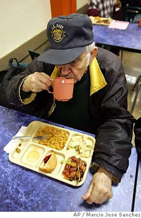 Bill Butler, a homeless veteran, eats lunch at St. Anthony's dining hall, a soup kitchen for the city's homeless, in San Francisco on Monday, Dec. 19, 2005. More Americans nationwide needed emergency food and shelter last year, according to the results of a 24-city survey released Monday by the U.S. Conference of Mayors. Overall, requests for food assistance grew by 12 percent during the past year with 76 percent of the cities surveyed reporting an increase. (AP Photo/Marcio Jose Sanchez) Photo: MARCIO JOSE SANCHEZ