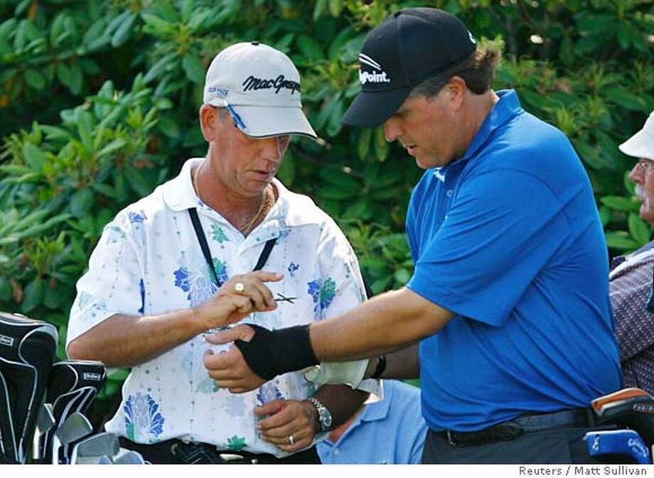 Phil Mickelson of the U.S. (R) has his left wrist wrap adjusted by Chip Carpenter on the ninth tee during a practice round for the 2007 US Open Championship golf tournament at the Oakmont Country Club in Oakmont, Pennsylvania, June 12, 2007. REUTERS/Matt Sullivan (UNITED STATES) Photo: MATT SULLIVAN