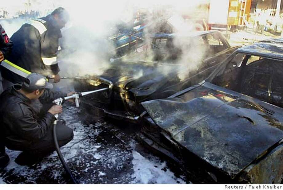 Iraqi firemen extinguish burning vehicles after a suicide bomb attack against a police colonel in Baghdad December 19, 2005. An Iraqi police colonel escaped assassination when a suicide car bomber detonated his explosives as the colonel's convoy was passing in the Iskan district. Two civilians were killed. The colonel, two of his bodyguards and five civilians were wounded. REUTERS/Faleh Kheiber 0 Photo: FALEH KHEIBER