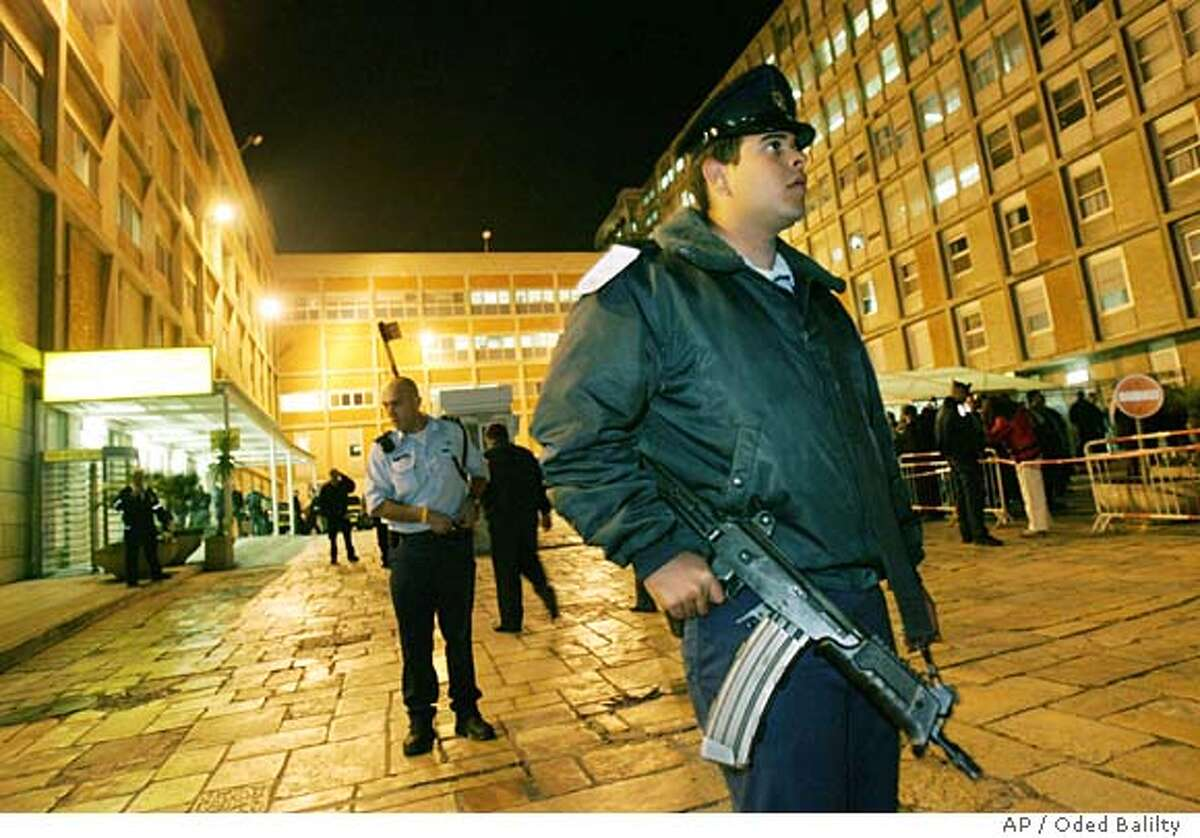 Police guard the Hadassa hospital in the outskirts of Jerusalem shortly after Israeli Prime Minister Ariel Sharon was rushed there Sunday Dec. 18, 2005. Sharon was taken to Jerusalem's Hadassah Hospital after nightfall Sunday, a hospital spokeswoman said, after feeling unwell while working in his office. Sharon was awake and undergoing medical tests, a hospital official said.(AP Photo/Oded Balilty)