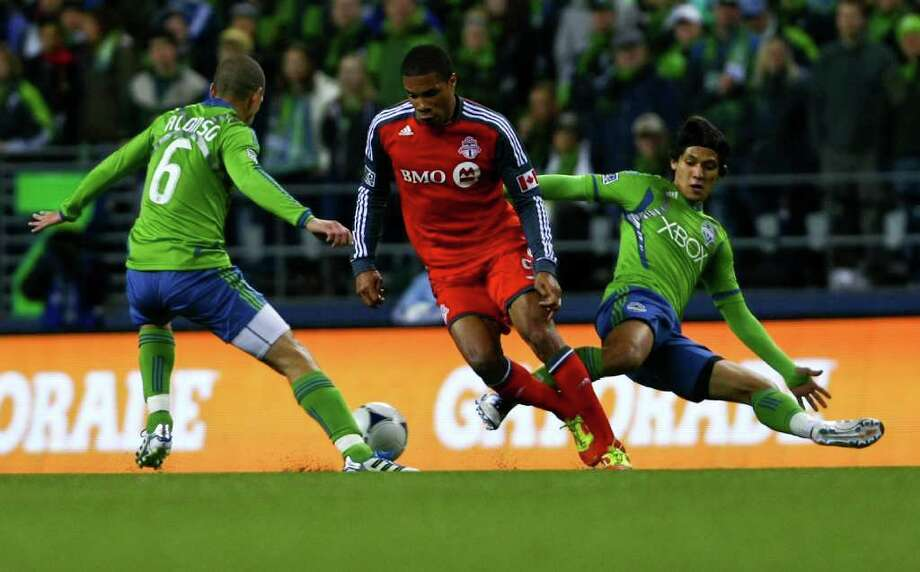 Alonso Osvaldo and Fredy Montero of the Seattle Sounders and Ryan Johnson of Toronto FC and fight for the ball during their game at CenturyLink Field in Seattle on Saturday, March 17, 2012. Photo: JOE DYER / SEATTLEPI.COM