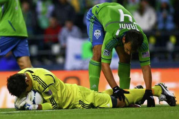 Seattle Sounders Goalie Michael Gspurning embraces the ball after preventing a goal while his teamate Patrick Ianni tries to avoid tripping over him, CenturyLink Field in Seattle on Saturday, March 17, 2012. Photo: JOE DYER / SEATTLEPI.COM