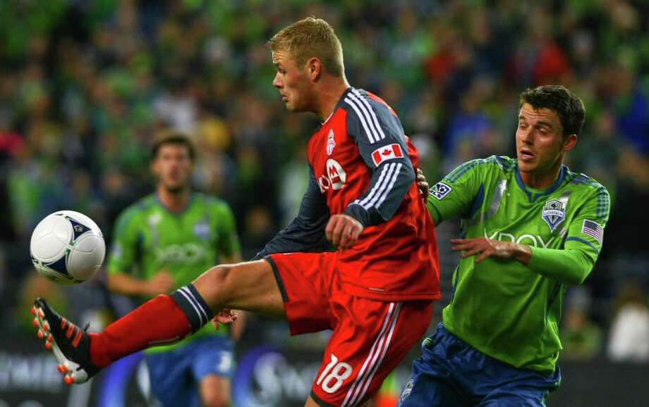 Toronto FC forward Nick Soolsma jumps in front of defender Marc Burch for the  ball during their game at CenturyLink Field in Seattle on Saturday, March 17, 2012. Photo: JOE DYER / SEATTLEPI.COM