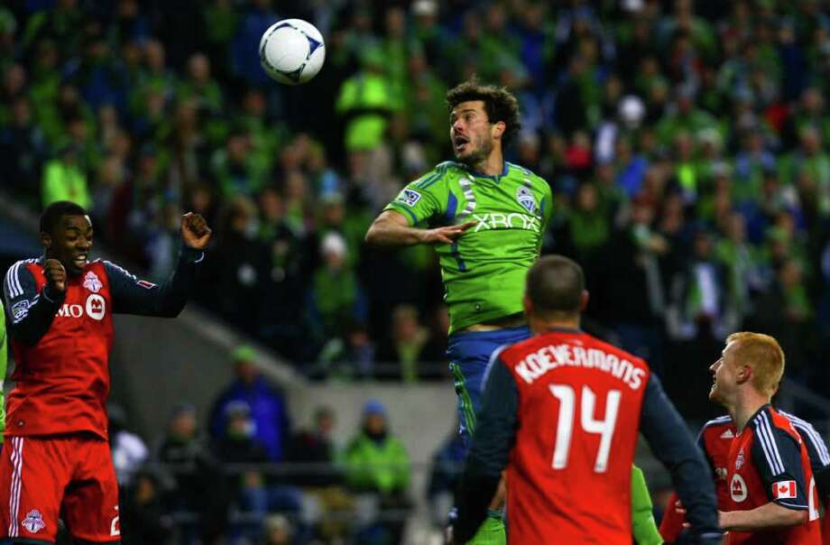 Brad Evans of the Seattle Sounders goes for a header against Toronto FC players at CenturyLink Field in Seattle on Saturday, March 17, 2012. Photo: JOE DYER / SEATTLEPI.COM