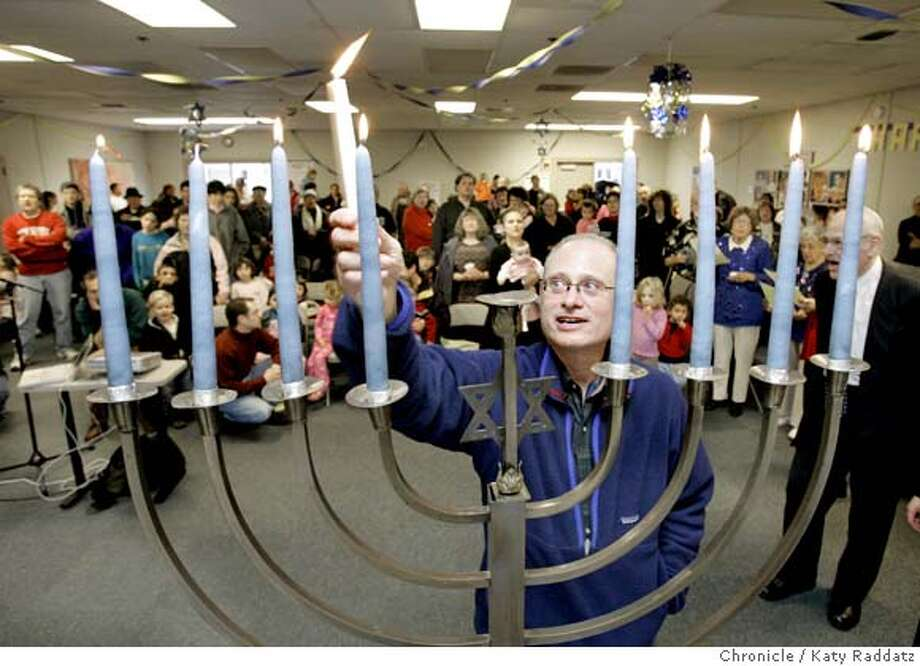LATKA19_023_RAD.JPG SHOWN: Lighting the Channukah menorah to show people how to do it in their own homes is Rabbi Raiskin of Peninsula Temple Shalom. The Peninsula Jewish Community has invited the community to a free Channukah celebration with latkes (this IS the correct spelling, dancing, and candle lighting. Photo taken on 12/18/05, in Foster City, CA.  By Katy Raddatz / The San Francisco Chronicle MANDATORY CREDIT FOR PHOTOG AND SF CHRONICLE/ -MAGS OUT Photo: Katy Raddatz