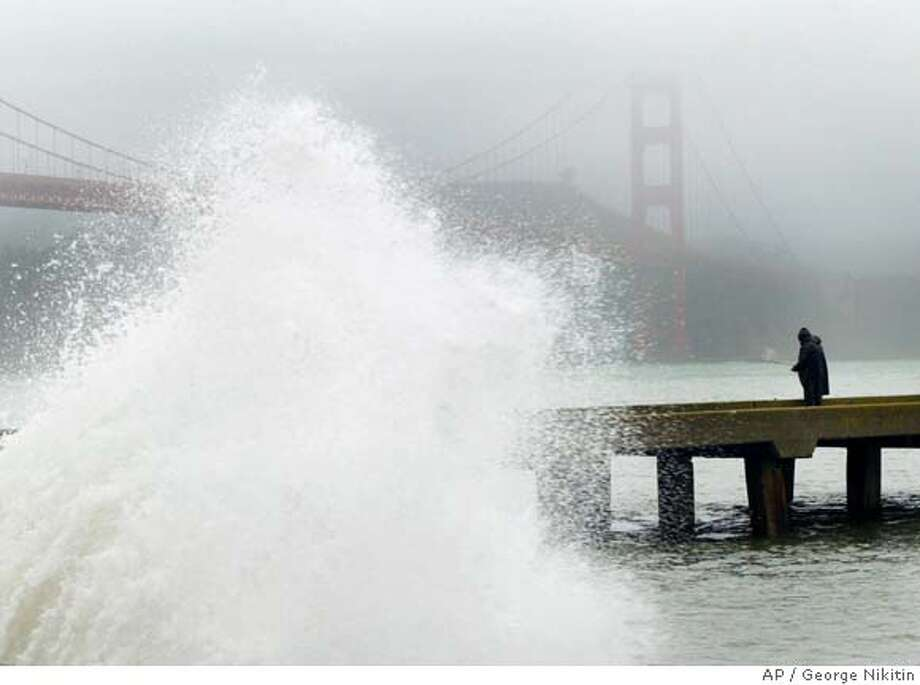 An unidentified man fishes off a pier as a large wave explodes off the breakwater near the Golden Gate Bridge in San Francisco, on Sunday Dec. 18, 2005. A large storm hit northern California producing strong winds, heavy rains, large surf and flooding. (AP Photo/George Nikitin) Photo: GEORGE NIKITIN