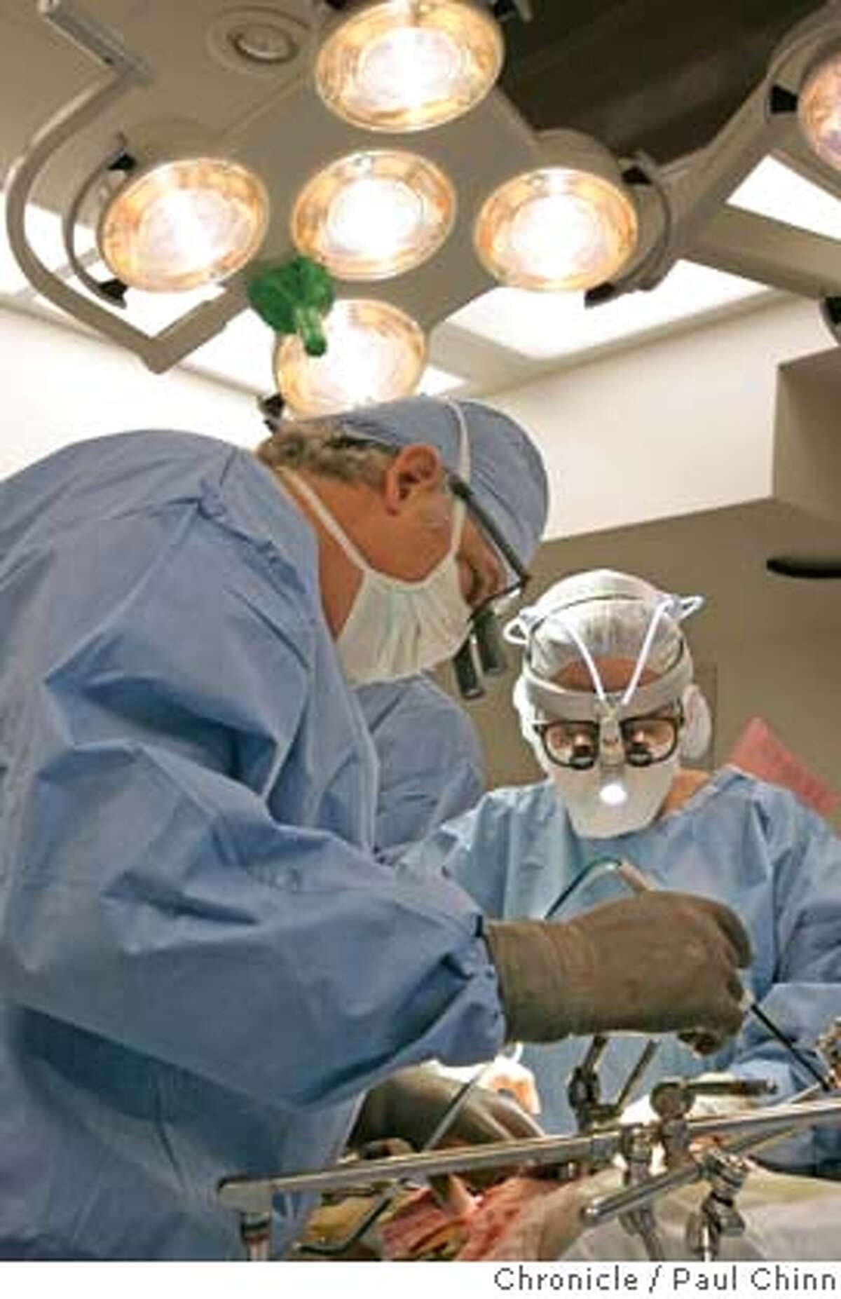 Transplant surgeons - and husband and wife - John Roberts (left) and Nancy Ascher remove a liver from a living donor at UCSF Medical Center on 11/3/05 in San Francisco, Calif. PAUL CHINN/The Chronicle