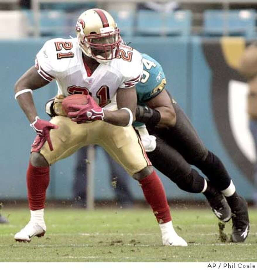 San Francisco 49ers running back Frank Gore, left, is tackled by Jacksonville Jaguars defender Mike Peterson, right, during the second quarter of their National Football League game, Sunday, Dec. 18, 2005, in Jacksonville, Fla. (AP Photo/Phil Coale) Photo: PHIL COALE