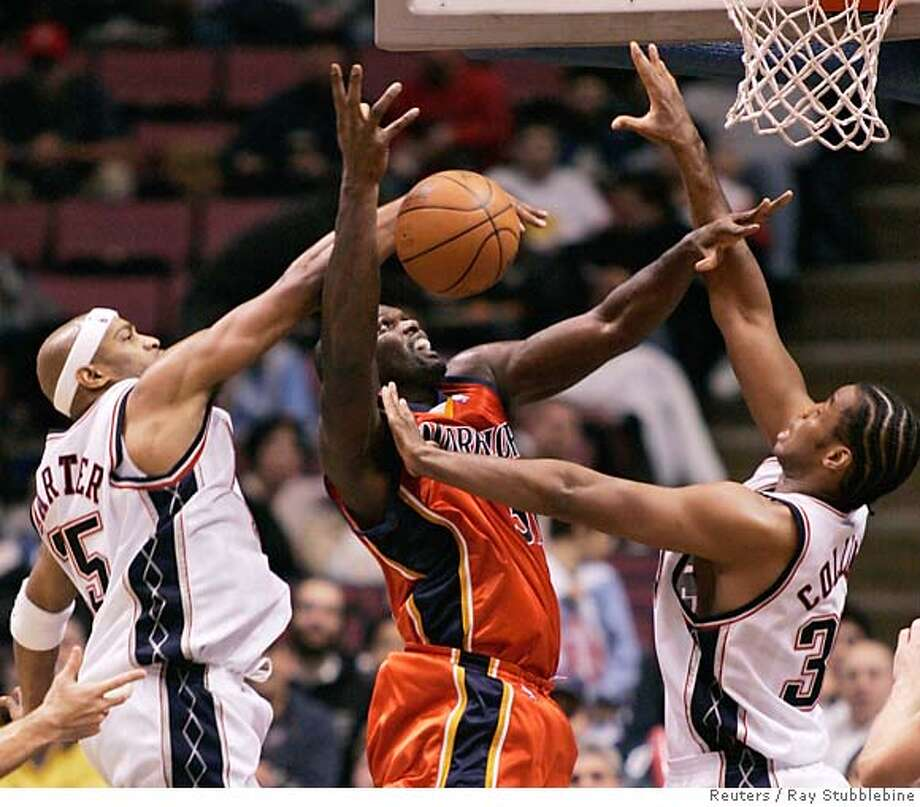 New Jersey Nets guard Vince Carter (L) reaches to slap away a shot by Golden State Warriors center Adonal Foyle (C) as he is guarded by Nets forward Jason Collins in the second quarter of their NBA game in East Rutherford, New Jersey December 18, 2005. REUTERS/Ray Stubblebine Photo: RAY STUBBLEBINE