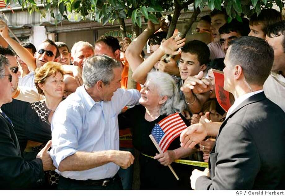 U.S. President George Bush talks to a women holding an American flag during a stop in Fushe Kruje, Albania, Sunday, June 10, 2007. (AP Photo/Gerald Herbert) Photo: Gerald Herbert