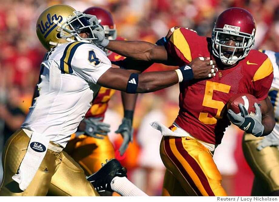 University of Southern California tailback Reggie Bush (5) breaks a tackle from UCLA's Jarrad Page during the first quarter of their NCAA game in Los Angeles, December 3, 2005. REUTERS/Lucy Nicholson Ran on: 12-11-2005 Ran on: 12-11-2005 Ran on: 12-11-2005 0 Photo: LUCY NICHOLSON