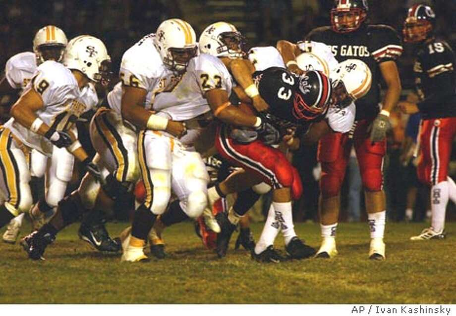 Danny Bates, 33, of the Los Gatos Wildcats, is tackled by William Taufoou , 23, and many other St. Francis Lancers at Los Gatos Highschool on Friday Semptember 19, 2003. (AP photo/Ivan Kashinsky)