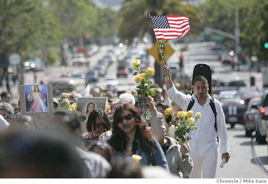 Marco Camacho, right with flag, joins Irish American Catholics, Mission Dolores congregation members, and other immigration reform supporters for a procession from Mission Dolores to St. Mary's Cathedral in San Francisco, CA, on Saturday, June, 9, 2007. photo taken: 6/9/07  Mike Kane / The Chronicle *Marco Camacho Photo: MIKE KANE