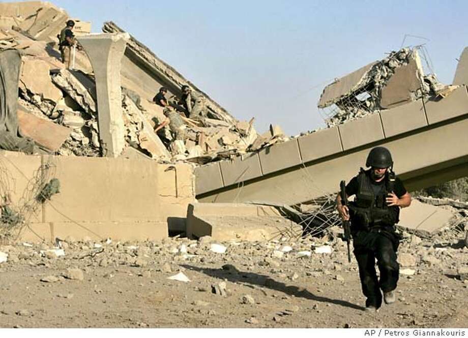 U.S. troops and private security guards, in black, work to remove concrete rubble from atop wounded soldiers, at a bridge destroyed by an apparent suicide vehicle bomber on Sunday, June 10, 2007, outside Mahmoudiya, about 30 kilometers (20 miles) south of Baghdad, Iraq.An apparent suicide car bomber took aim at a U.S. convoy carrying demolition experts, collapsing a major highway overpass south of Baghdad and trapping American soldiers in the rubble. (AP Photo/Petros Giannakouris). Photo: PETROS GIANNAKOURIS