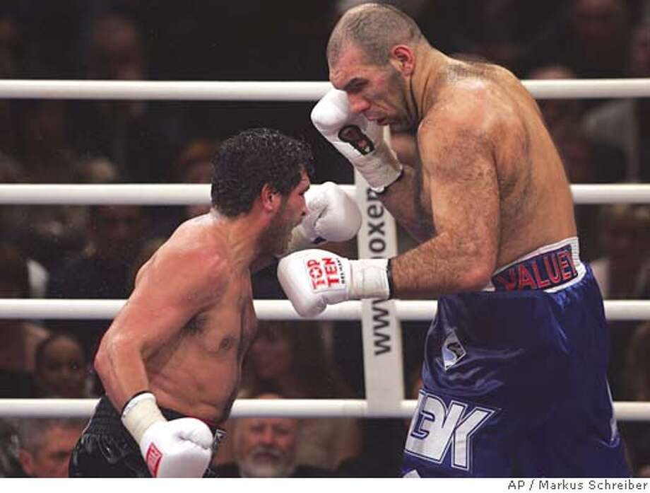 U.S. John Ruiz, left, and challenger Nikolay Valuev from Russia fight during a WBA heavywight world championship fight in Berlin early Sunday morning, Dec. 18, 2005. Valuev won the WBA heavywight world championship fight by points in 12 rounds. (AP Photo/Markus Schreiber) Photo: MARKUS SCHREIBER