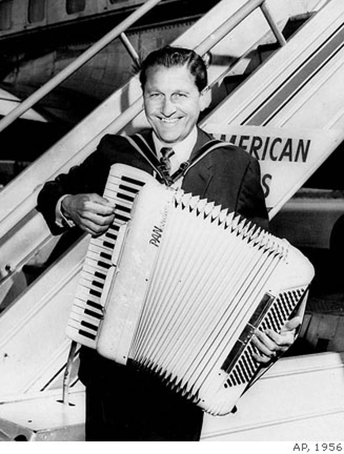WELK/C/18AUG99/DD/AP-Bandleader Lawrence Welk arrives at Idlewild Airport aboard an Amerian Airlines nonstop flagship with his favorite instrument, ready to pour out some music, May 29,1956. Welk had reason to smile: he was selected