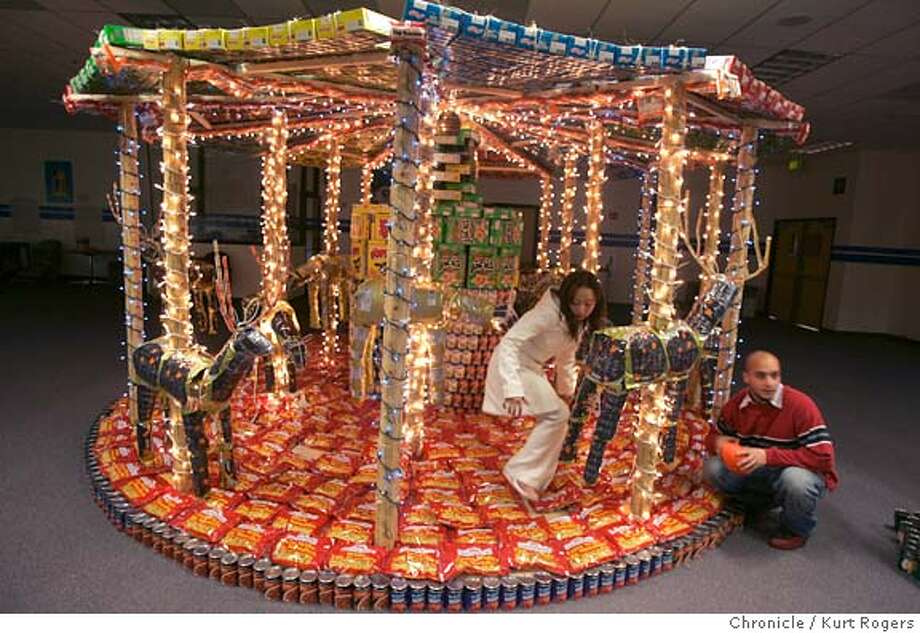 Each year, Cypress Semiconductor holds a contest for the most elaborate sculpture of canned food. It's part of a big canned food drive. This years winner was in building three where Maria Ly and Karl Haddad work on fixing some out of place objects in the carousel.  Kurt Rogers SAN JOSE SFC  The Chronicle FOOD_0004_kr.JPG MANDATORY CREDIT FOR PHOTOG AND SF CHRONICLE/ -MAGS OUT Photo: Kurt Rogers