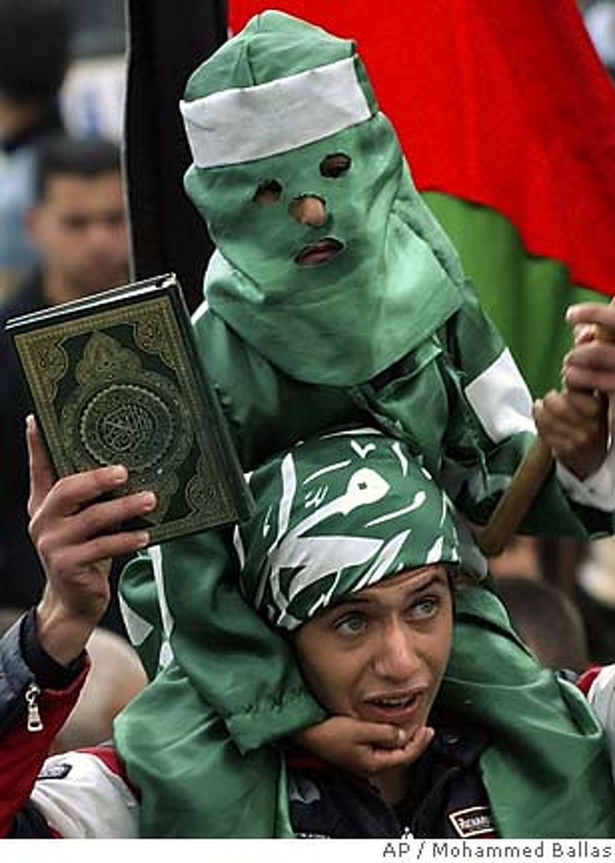 Hamas supporters, one holding a copy of the Quran and a child on his shoulders, take part in a rally celebrating the group's strong showing in municipal elections in the West Bank town Jenin, Friday Dec. 16, 2005. The Hamas militant group won local elections in the West Bank's largest cities, according to preliminary results released Friday, dealing a harsh blow to the ruling Fatah party just six weeks ahead of a parliamentary poll.(AP Photo/Mohammed Ballas)