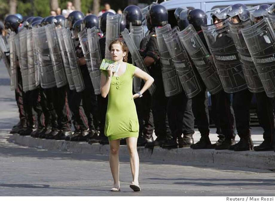 A tourist walks in front of anti-riot Carabinieri military police as they wait for a demonstration against the visit by U.S. President George W. Bush in Rome June 9, 2007. Bush met Pope Benedict on Saturday and told the pontiff he believed the G8 summit in Germany had been a success. REUTERS/Max Rossi (ITALY) 0 Photo: MAX ROSSI