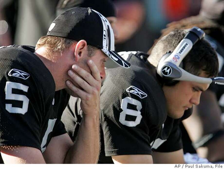 ** FILE ** Oakland Raiders quarterbacks Kerry Collins, left, and Marques Tuiasosopo, right, sit on the bench during an NFL football game against the San Diego Chargers, Oct. 16, 2005, in Oakland, Calif. Tuiasosopo's chance to prove himself lasted just one week. Tuiasosopo was sent back to the bench Wednesday, Dec. 14, 2005, when the Raiders made another quarterback change, moving Collins back into the starting role for Sunday's game against Cleveland. (AP Photo/Paul Sakuma) EFE OUT Photo: PAUL SAKUMA