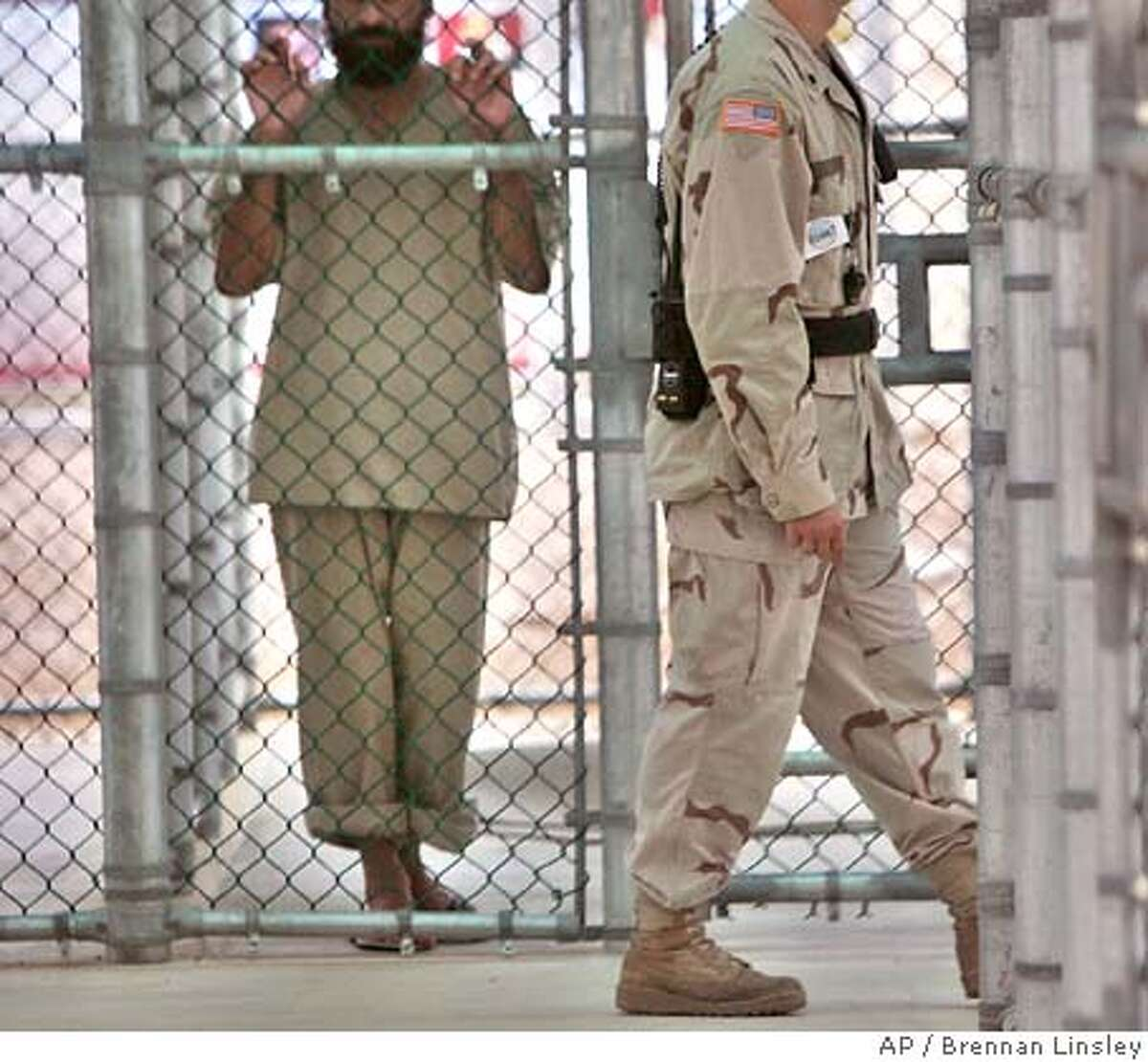 In this June 26, 2006 file photo, reviewed by US military officials, a detainee, name, nationality, and facial identification not permitted, holds onto a fence as a U.S. military guard walks past, within the grounds of the maximum security prison at Camp 5, at the Guantanamo Bay U.S. Naval Base, Cuba. President George W. Bush on Wednesday Sept. 6 acknowledged the existence of CIA prisons around the world, and said 14 high-value terrorism suspects, including the mastermind of the Sept. 11 attacks, have been transferred from this system to the military prison at Guantanamo Bay for eventual trials. (AP Photo/Brennan Linsley, Pool) Ran on: 09-08-2006 A detainee holds onto a fence at the Guantanamo Bay detention center, which took custody of prisoners from CIA facilities this week. Ran on: 09-08-2006 A detainee holds onto a fence at the Guantanamo Bay detention center, which took custody of prisoners from CIA facilities this week. FILE PHOTO FROM JUNE 26 2006 TO BE MOVED SEPT 6. EDS: PHOTO HAS BEEN REVIEWED BY US MILITARY OFFICIALS