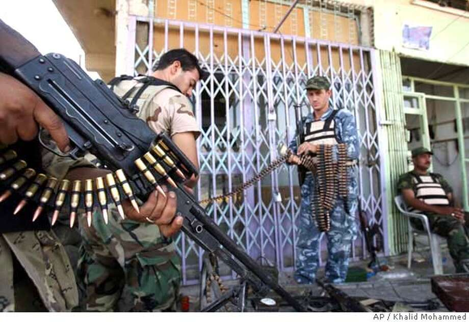 Iraqi police commando ready themselves as clashes erupted between Iraqi security forces and gunmen in Amil district in Baghdad, Iraq, Saturday, June 9, 2007. Iraqi security forces are targets of sniper and bomb attacks regularly in the area. (AP Photo/Khalid Mohammed ) Photo: KHALID MOHAMMED
