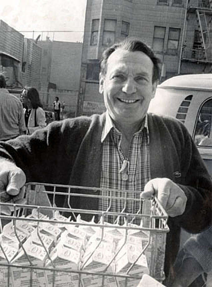 Fred Polizzi holds a crate of milk for a food giveaway in front of his old liquor store on Sixth Street on Dec. 17, 1980. Chronicle file photo, 1980 by Peter Breinig