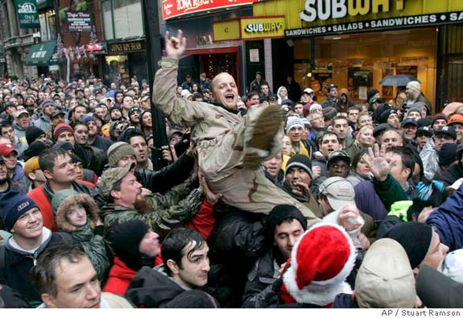 An unidentified fan of controversial radio shock jock Howard Stern is tossed by the waiting crowd outside his radio station before he appeared to wish them farewell on his last day of broadcasting for Infinity Broadcasting, Friday, Dec.16, 2005, in New York. On Jan. 9, Stern makes his move to satellite radio.(AP Photo/Stuart Ramson) Ran on: 12-17-2005  Shock jock Howard Stern, a New York radio star for 20 years, takes a &quo;victory lap&quo; in Times Square. Photo: STUART RAMSON