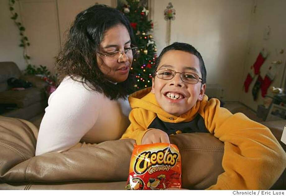 sos16_034_el.JPG  A SOS story about Sandra Alvarenga, a working mother who wants enough money to pay for jaw surgery for her son William, 10. At home in San Rafael with his favorite snack, Cheetos. Photographer:� Eric Luse / The Chronicle MANDATORY CREDIT FOR PHOTOG AND SF CHRONICLE/ -MAGS OUT Photo: Eric Luse