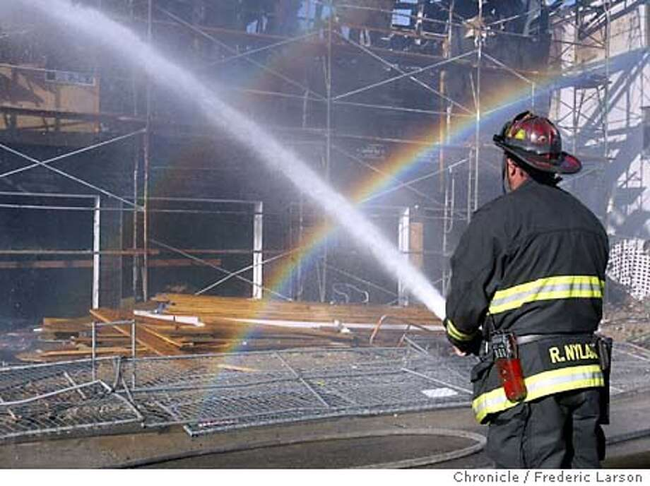 . A Oakland firefighters sprays water on a five structures have been destroyed or damaged in a fire that began near I-580 in Oakland. The six alarm blaze began at about 2:30 this afternoon off I-580 near MacArthur and Beaumont. Embers from the blaze set trees on fire near the freeway and ignited a house a half-block away. James Lee with the Oakland Fire Department said a warm air inversion caused winds to whip through the area, when sent embers onto other nearby structures. It is not clear how the fire started, but the three story apartment building where it began was under construction, and no one was inside. Traffic was backed up through the area during the fire because of all the smoke, and the CHP tried to keep people from stopping to watch the blaze. There were no reports of injuries FREDERIC LARSON / The Chronicle Photo: FREDERIC LARSON