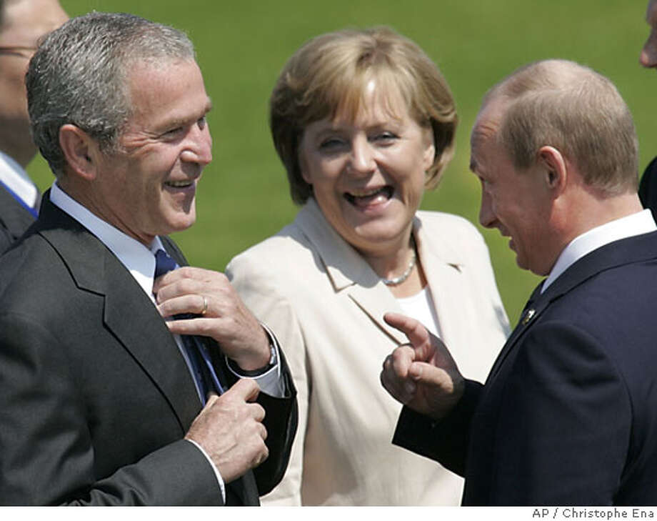 U.S. President George Bush, left, German Chancellor Angela Merkel, center and Russian President Vladimir Putin, right share a laugh during a photo call at the G8 summit in Heiligendamm, Friday, June 8, 2007. The leaders of the G8 nations are holding their annual summit in the historic Heiligendamm Baltic sea resort on June 6-8, 2007. (AP Photo/ Christophe Ena) Photo: CHRISTOPHE ENA