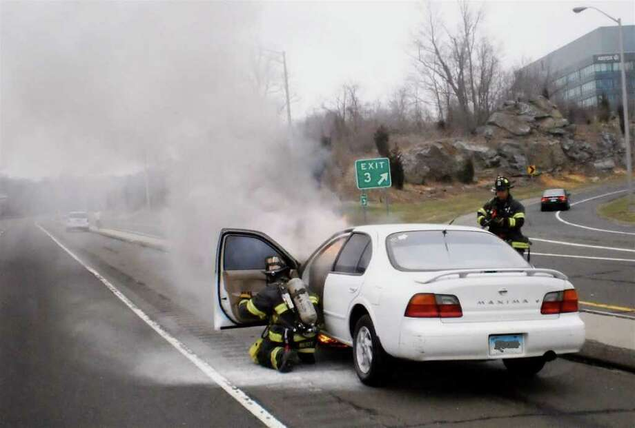 Firefighters extinguish a 2005 Nissan Maxima that caught fire while traveling north on the Route 7 Connector Sunday morning. The driver was not injured, according to fire officials. Photo: Norwalk Fire Department