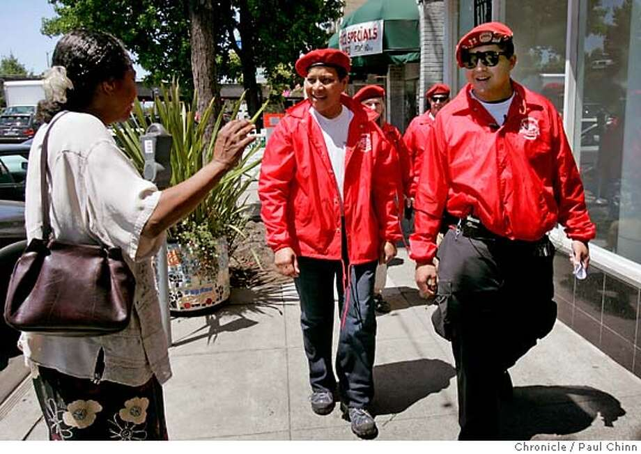 Joi Myers waves to Guardian Angels Nic Montesclaros (center) and Erick Wong who began patrolling the Lakeshore neighborhood in Oakland, Calif. on Friday, June 8, 2007 after numerous reports of criminal activity has plagued the area in recent weeks.  PAUL CHINN/The Chronicle  **Joi Myers, Nic Montesclaros, Erick Wong Photo: PAUL CHINN