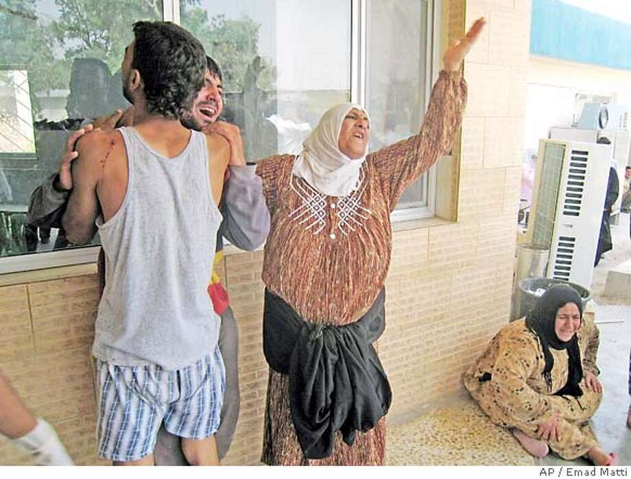 Iraqi relatives react outside a hospital in Kirkuk, 290 kilometers (180 miles) north of Baghdad, Iraq, on Friday, June 8,2007, after two suicide bombers with explosives vests blew themselves up Friday afternoon in the Shiite-dominated town of Dakok, about 45 kilometers (28 miles) south of Kirkuk, killing 13 civilians and wooded 14 others.(AP Photo/Emad Matti) Photo: EMAD MATTI
