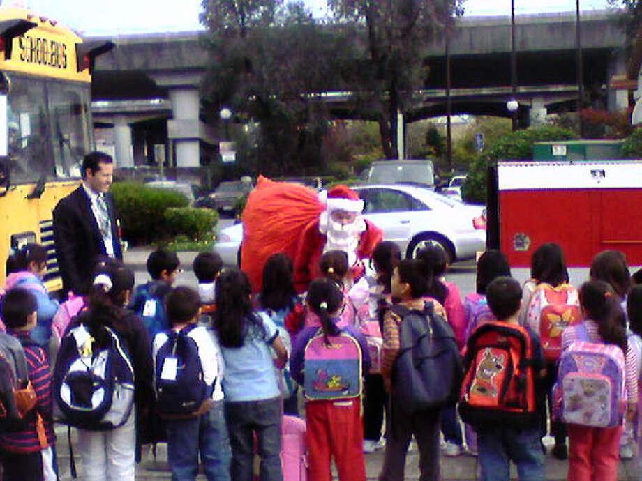 Members of the San Rafael Fire and Police departments played Santa during a toy give-away to kids from Bahia Vista School on Dec. 8. Photo: HO